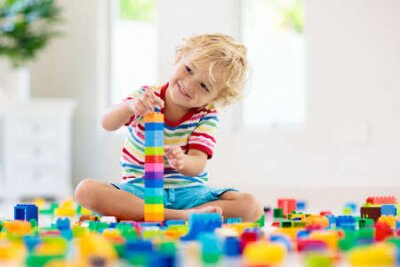 Fototapete Child playing with colorful toy blocks. Little boy building tower at home or day care. Educational toys for young children. Construction block for baby or toddler kid. Mess in kindergarten play room.