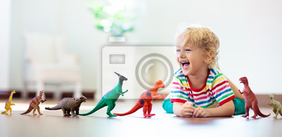 Fototapete Child playing with toy dinosaurs. Kids toys.