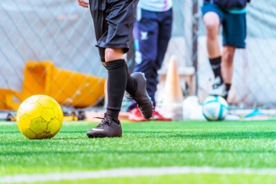 Fototapete Children is training and dibbling ball in soccer training