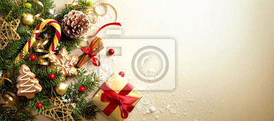 Fototapete Christmas decoration composition on light gold background with beautiful Golden gift box with red ribbon, fir branches, cones, stars, Christmas cookies,cinnamon, top view, copy space, banner format.