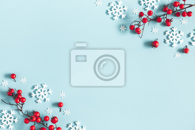 Fototapete Christmas or winter composition. Frame made of snowflakes and red berries on pastel blue background. Christmas, winter, new year concept. Flat lay, top view, copy space