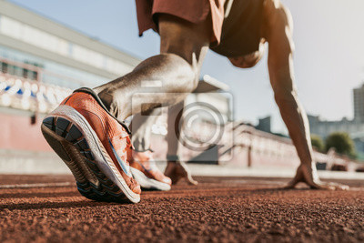 Fototapete Close up of male athlete getting ready to start running on track . Focus on sneakers