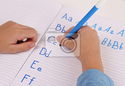 Close up on childs hands  Writing  the alphabet with Pencil . Kid, homework, education concept. Selective focus image