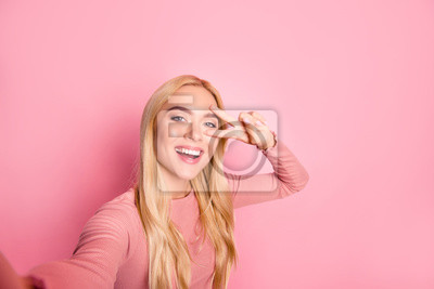 Fototapete Close up photo of happy adorable woman with beaming smile. She is taking selfie and showing two fingers against pink background