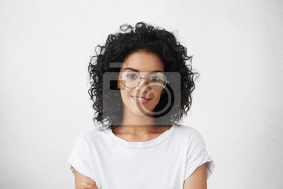 Fototapete Close up Studio Schuss schöne junge gemischte Rasse Frau Modell mit lockigen dunklen Haaren Blick auf Kamera mit charmanten süßen Lächeln während posiert gegen weiße leere Kopie Raum Wand für Ihren In