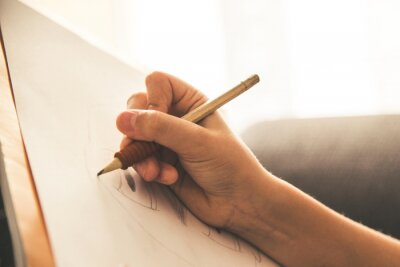 Fototapete Close up view of a young hand drawing on a white sheet. Kid hold a black wooden pencil and draw something on a warm orange light at home. Children writing on a paper. Teen drawing freehand a manga.