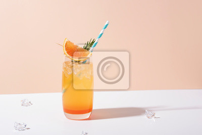 Fototapete Cold and refreshing orange punch cocktail with orange slice on color background. summer drink.