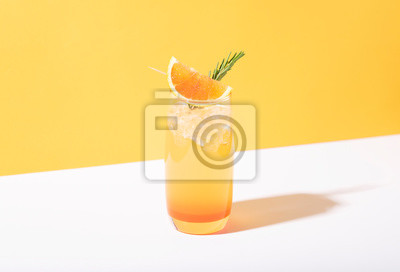 Fototapete Cold and refreshing orange punch cocktail with orange slice on yellow background. summer drink.