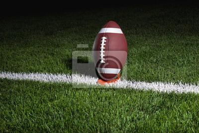College Football auf einem Tee in der Nacht