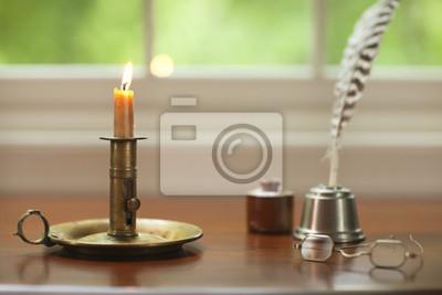 Colonial Kerze, Feder und Gläser auf dem Schreibtisch mit Fenster