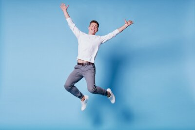 Fototapete Colorful studio portrait of happy young man jumping against blue background.