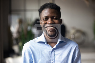Fototapete Confident smiling young african businessman looking at camera in office