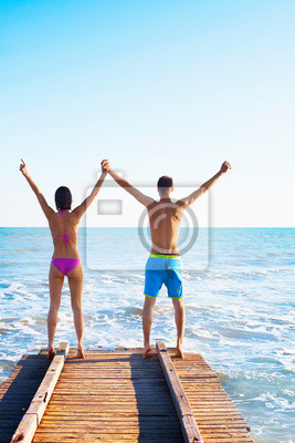 Couple Holding Hands Up at Wooden Pier