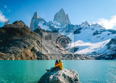 Fototapete Couple in love at Mount Fitzroy. Scenic view of snowcapped mountain tops of Patagonia trek. Blue sky, turquoise lake and scenic rock landscape. Shot in Argentina. Nature, travel, adventure, hiking.