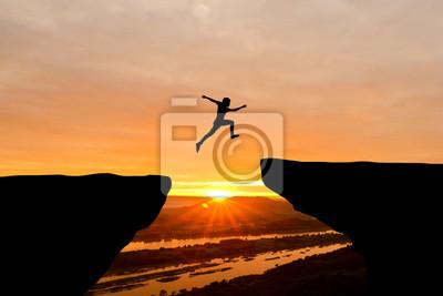 Fototapete Courage Mann springt über Klippe auf Sonnenuntergang Hintergrund, Business-Konzept Idee