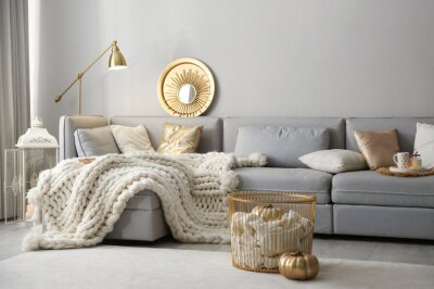 Fototapete Cozy living room interior with knitted blanket on comfortable sofa