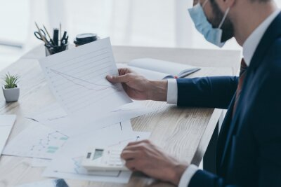 Fototapete cropped view of businessman in medical mask working with documents at workplace