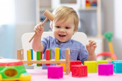Fototapete cute toddler baby playing with wooden hammer block toy