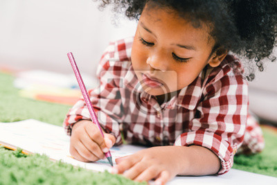 Fototapete Cute young African American kid girl drawing or painting with colored pencil. Kindergarten children education, back to school, or preschool child study at home concept