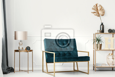 Fototapete Dark green sofa with golden frame by a white wall with molding in an elegant living room interior with expensive decor