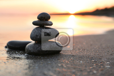 Fototapete Dark stones on sand near sea at sunset, space for text. Zen concept