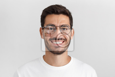 Fototapete Daylight portrait of young handsome caucasian man isolated on grey background, dressed in white t-shirt and round eyeglasses, looking at camera and smiling positively