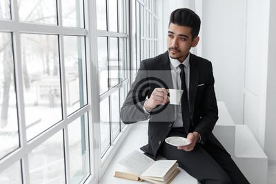 Fensterbank Zum Sitzen denken geschäftsmann in anzug sitzen auf fensterbank und getränke