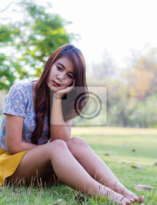 Depressive junge Frau sitzt allein im Garten