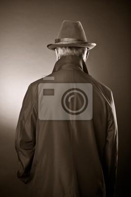 Der Mann in einem Regenmantel und einen Hut. Die Heckansicht
