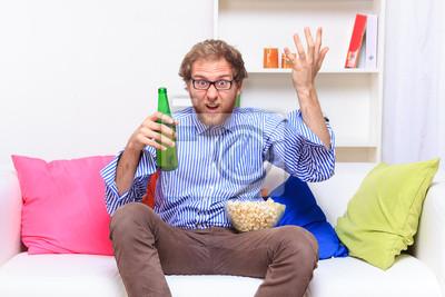 Dissatisfacted Mann auf der Couch beim Fernsehen