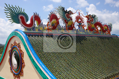 Dragons statue on the roof of Chinese temple with cloud blue sky.