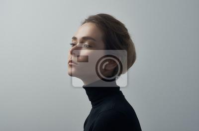 Fototapete Drastisches Porträt eines jungen schönen Mädchens mit Sommersprossen in einem schwarzen Rollkragen auf weißem Hintergrund im Studio