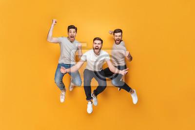Fototapete Drei junge glückliche Männer, die zusammen springen