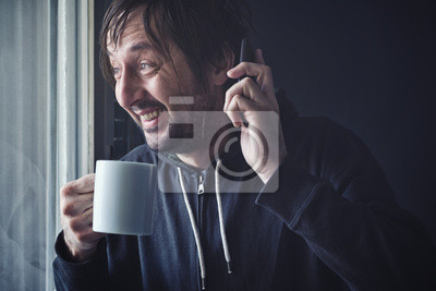 Fototapete Drinking Coffee And Talking on Mobile Phone in Morning