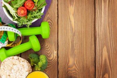 Fototapete Dumbells, Maßband und gesundes Essen über Holztisch
