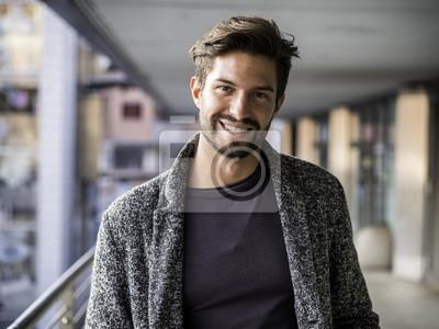Fototapete Ein hübscher junger Mann in der städtischen Einstellung in der europäischen Stadt, Stellung und Lächeln zur Kamera glücklich