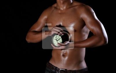 Ein Hunky asiatische Mann im Besitz einer Uhr in seinen Händen,