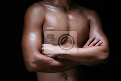 Ein hunky junger asiatischer Mann, der seine Hände mit muskulöser Brust faltet