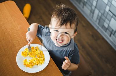 Fototapete ein Kind in einem T-Shirt in der Küche isst ein Omelett, eine Gabel