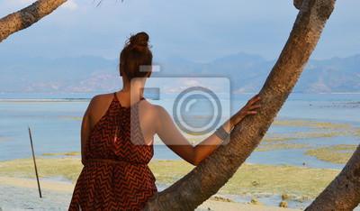 Ein Mädchen bilden hinter am Strand mit Blick auf den Ozean. Ein blauer Himmel und blauem Wasser im Hintergrund sind, die die Schönheit des Sommers. So um die Welt reisen.