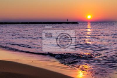 Fototapete Ein ruhiger, ruhiger Sonnenuntergang am Meer und sanfte Wellen spritzen am Strand.