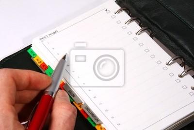 Eine Hand schriftlich in einem Leder-Organizer mit einem roten Stift
