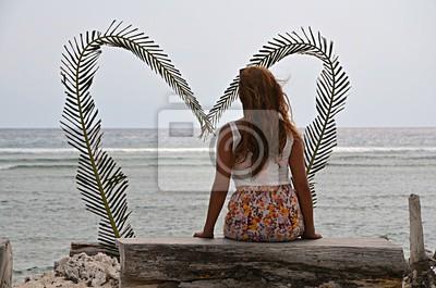 Eine junge alleinstehende Frau ist auf dem Strand sitzt vor einem großen Herzen, ohne eine Beziehung oder einem Partner / Freund. Das macht sie traurig, weil sie allein / einsam und sucht nach Liebe.