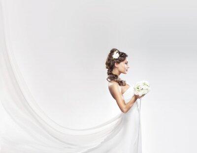 Fototapete Eine junge kaukasische Braut posiert in einem weißen Kleid mit Blumen