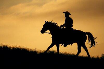 Fototapete Eine Silhouette ein Cowboy und Pferd zu Fuß auf eine Wiese mit einer orange und gelben Hintergrund Himmel.