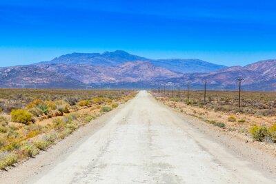 Fototapete Eine unbefestigte Straße in der Karoo neben neben Bauernhof Zäune.