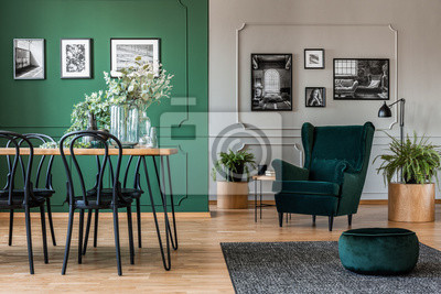 Fototapete Elegant bottle green dining room with wooden table with black chairs and emerald green armchair and pouf