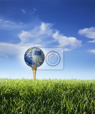 Erde als Golfball auf Tee mit Gras, blauer Himmel