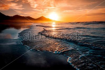 Fototapete Erstaunlicher Strand-Sonnenuntergang mit endlosem Horizont und einsamen Figuren in der Ferne und unglaublichen Schaumwellen. Vulkanhügel im Hintergrund in idyllischen warmen Farben.