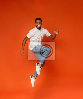 Fototapete Excited african-american man jumping on orange background